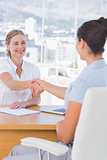 Cheerful interviewer shaking hand of an applicant