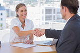 Cheerful interviewer shaking hand of an interviewee