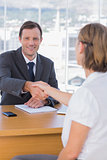 Businessman giving a handshake to a job applicant