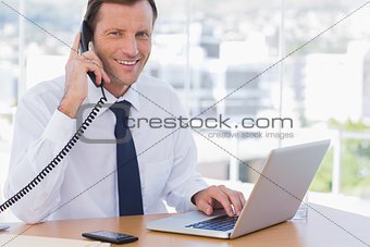 Smiling businessman posing while he is on the phone