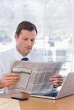 Serious businessman reading a newspaper