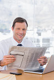 Smiling businessman reading a newspaper