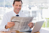Cheerful businessman reading a newspaper