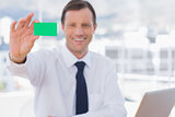 Smiling businessman holding a green business card