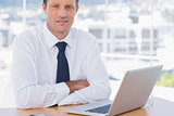 Businessman with arms folded on his desk