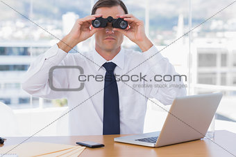 Businessman using binoculars in his office