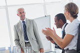 Colleagues applauding smiling manager during a meeting