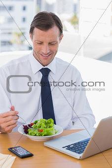 Smiling businessman eating a salad on his desk