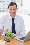 Cheerful businessman eating a salad on his desk