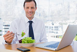 Happy businessman eating a salad on his desk