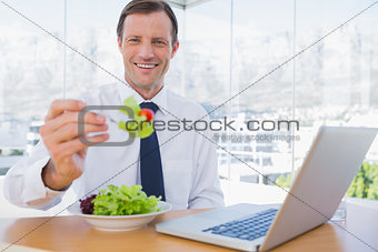 Smiling businessman eating a salad