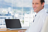 Smiling businessman sitting in front of a laptop
