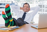 Smiling businessman relaxing with feet on his desk