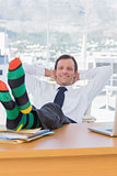 Cheerful businessman relaxing with feet on his desk