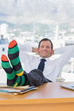 Happy businessman relaxing with feet on his desk