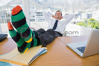 Business having a nap with feet on his desk