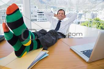 Smiling businessman having a nap with feet on the desk