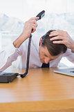 Irritated businessman holding the telephone