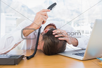 Irritated businessman holding the phone