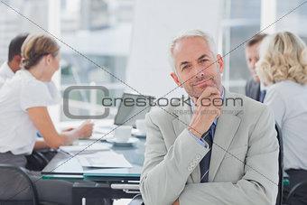 Smiling businessman posing in the boardroom