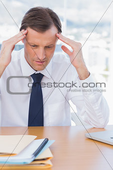 Anxious businessman holding his head