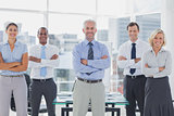 Team of smiling business people standing with arms folded