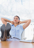 Pretty businesswoman relaxing in her office