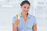 Happy businesswoman holding flute with champagne