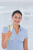 Brunette businesswoman raising a flute of champagne