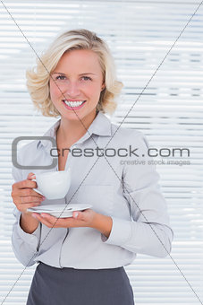 Blond businesswoman holding a cup