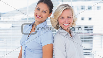 Attractive businesswomen standing back to back