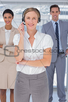 Cheerful woman with headset standing in front of business people