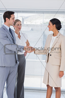 Business people shaking hands in bright office