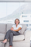 Cheerful businesswoman sitting on couch
