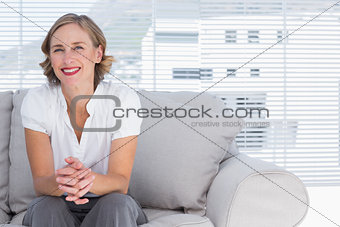 Blonde businesswoman sitting on couch