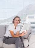 Businesswoman sitting on couch and holding newspaper