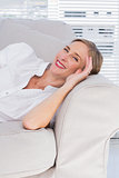 Cheerful businesswoman lying on sofa