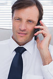 Portrait of a serious businessman talking on phone