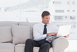Confident businessman sitting on couch