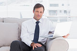 Businessman sitting on couch looking at camera