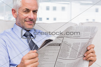 Smiling businessman holding a newspaper