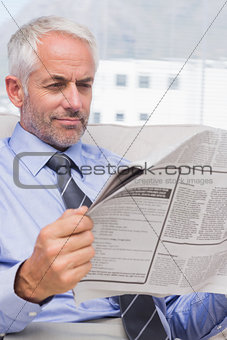 Attractive businessman reading a newspaper on couch
