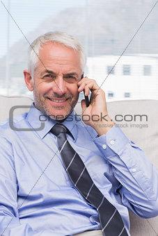 Smiling businessman calling on smartphone