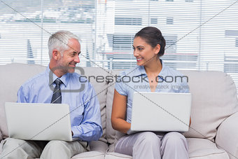 Business people using their laptops and smiling at each other