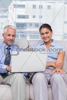 Business people with laptop smiling at camera sitting on couch