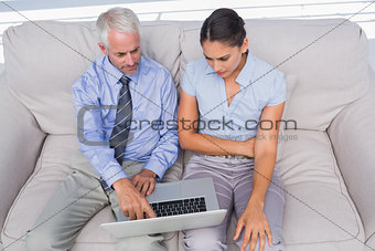 Business people using laptop on the couch