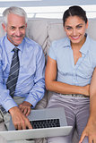 Business people using laptop on the couch and smiling up at camera