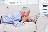 Businessman lying on sofa with laptop