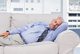 Businessman lying on sofa asleep