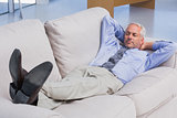 Businessman lying on sofa with his feet up